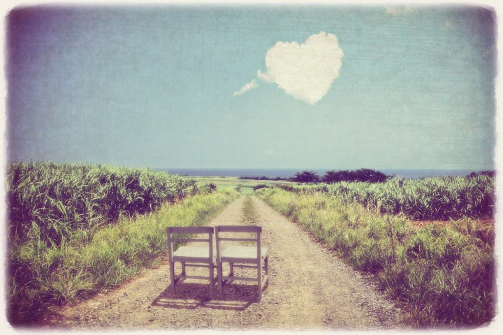 さとうきび畑の中を海に続く道と白い椅子とハートの雲