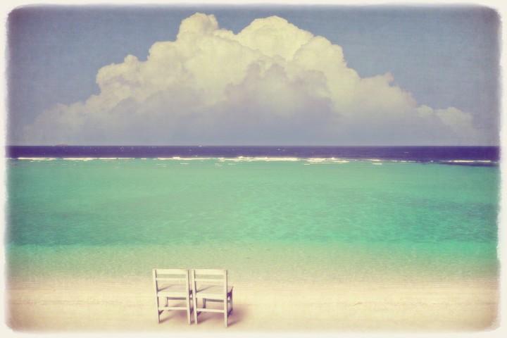 白い椅子と入道雲と珊瑚礁の砂浜