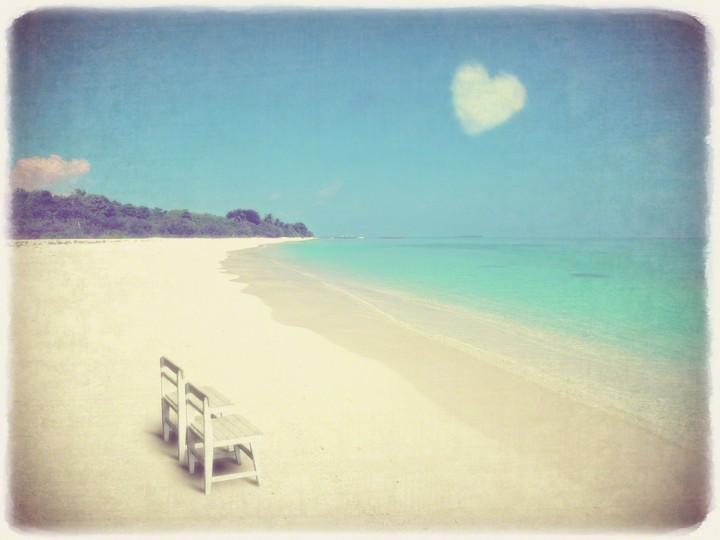 どこまでも続く珊瑚礁の砂浜の白い椅子とハートの雲