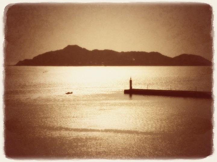 陽光に輝く海と灯台と船