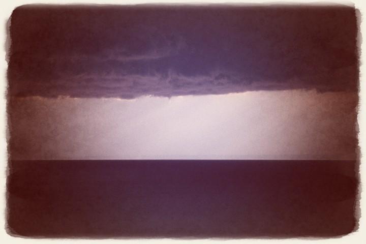 水平線と垂れ下がる雲の間の光芒