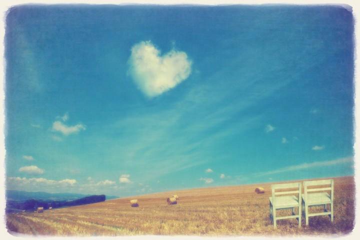 牧草ロールの丘の白い椅子と青空に浮かぶハートの雲